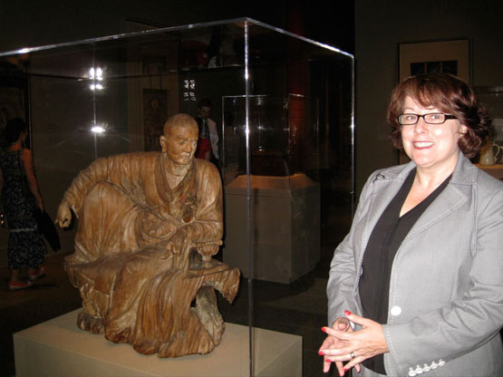 Denise Leidy, who organized the Buddhist part of the exhibition, stands in front of:  Arhat (Luohan)   Northern China   Yuan dynasty (1271–1368), mid–14th century / Wood with traces of pigment